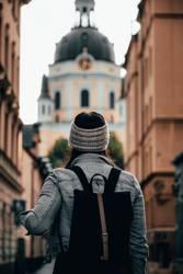 Frau mit Rucksack steht vor Kirche
