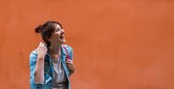 Lachende junge Frau vor Wand in orange