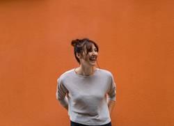 Junge lachende Frau vor oranger Wand