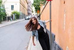 Schwingende Frau am Straßenschild