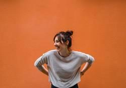 Lachende Frau vor orangem Hintergrund