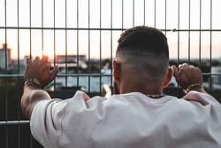 Junger Mann lehnt an Gitter