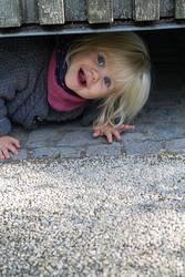 Kleines Mädchen schaut unter einem Zaun durch.