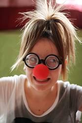 Mädchen mit Hornbrille und roter Clownnase
