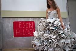 Junge Frau mit Kleid aus Zeitungen, fordert zum Lesen auf.