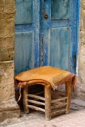 Kleiner Hocker mit Decke, steht vor blauer Tür, in der Medina.