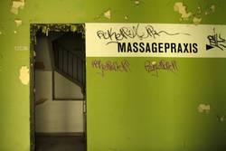Schriftzug Massagepraxis, auf alter, grüner Mauer