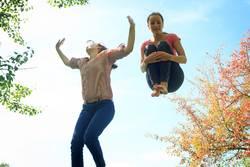 Zwei Mädchen hüpfen auf dem Trampolin, in der Natur.