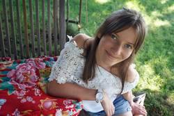 Junge Frau sitzt auf einer Wiese und lächelt