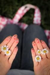 Bemalte Hände mit Gänseblümchen und Gesicht.