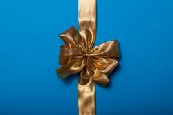 goldene Geschenkschleife auf blauem Hintergrund