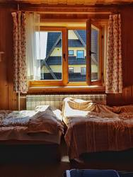 A warm moody room, wooden guesthouse, messy sheets, two beds