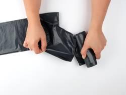 female hands tear off a black bag