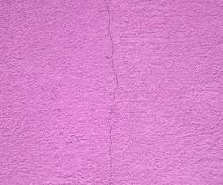 purple cement wall with a crack