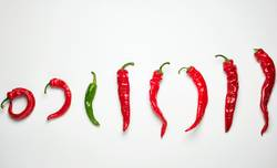 whole ripe red hot chili peppers on a white background