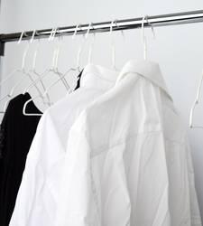white men's crumpled shirts hanging on a metal hanger