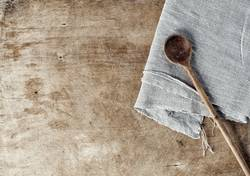 Brown wooden background with a wooden spoon