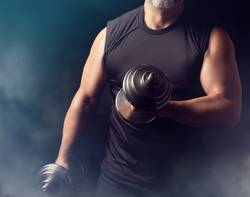 man in black clothes holds steel dumbbells