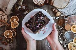 Teller mit Schokolade Sachertorte in weiblichen Händen