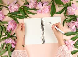 open empty notebook and two female hands