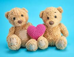 two brown teddy bears hold a red knitted heart