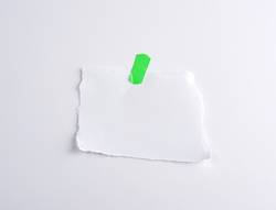 torn off white piece of paper glued to green velcro