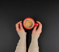 red creameric cup with black coffee in female hands