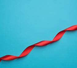 curled red satin ribbon on blue background