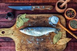 Fresh fish smelt for cooking on a kitchen board