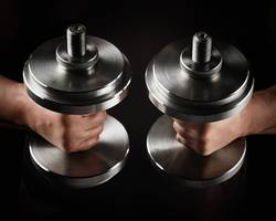 two steel typesetting dumbbells in male hands
