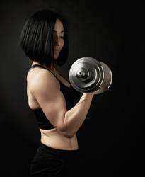 young woman holds steel type-setting dumbbells