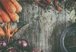 Frische Karotten und rote Zwiebel mit einer Bratpfanne