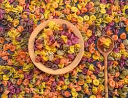 multicolored spiral raw pasta fusilli in a wooden bowl