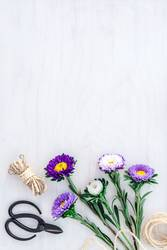 Bouquet of asters on white wooden background