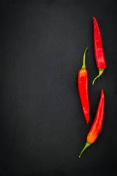 Three red chili peppers on dark background