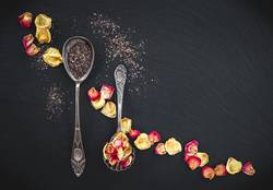 Silver spoons with floral tea and rose petals