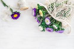 Asters in a mesh bag on white wooden background