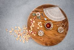 Vintage wooden table with tea and rose petals