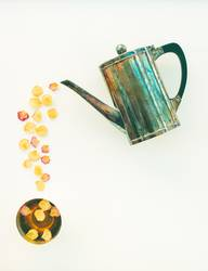 Vintage teapot and cup of tea with rose petals