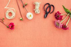 Florist workspace on peach colored canvas background