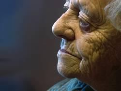 weißhaarige Seniorin mit nachdenklichem Blick