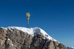 Golden summit cross at Zugspitze, Bavaria, Germany, wintertime