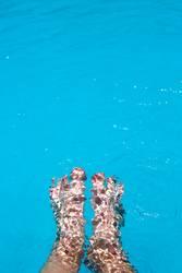 Splashing female feet in a swimming pool