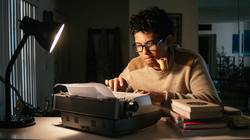Young man working in front of a typewriter