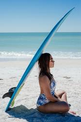 A young woman sitting under a surfboard