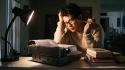 A young man sitting in front of a typewriter