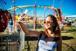 A woman taking a selfie at an amusement park