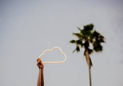An arm holding up a cloud neon sign