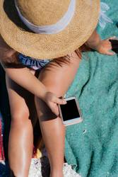 A young woman texting on the beach