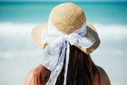 Young woman in a hat facing the beach